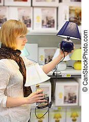 Blonde girl wearing scarf compares two table lamps in shop;...