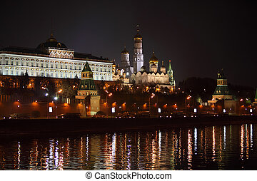 Moscow Kremlin with beautiful illumination at dark night in Russia; military equipment on road