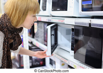 Blonde girl wearing scarf opens microwave in shop; shallow...