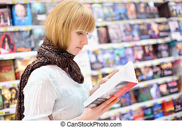 Blonde girl wearing scarf reads book in supermarket; shallow...