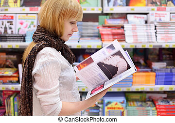 Blonde girl wearing scarf thumbs book in supermarket; shallow depth of field