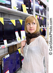 Blonde girl wearing scarf thinks about buying TV in supermarket; shallow depth of field