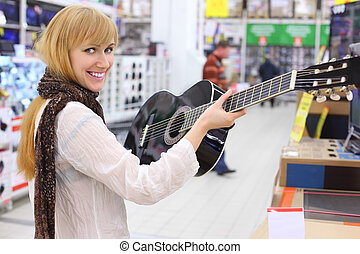 Happy girl wearing scarf holds guitar in supermarket;...