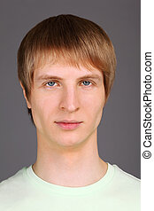 portrait of young blond man wearing light green T-shirt on...