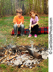 Two children sit around campfire and poke by sticks into...