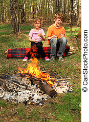 Two children sit near campfire and hold in their hands...