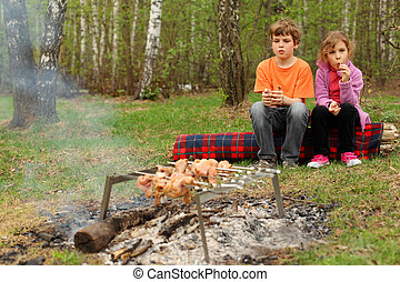 Two children sit near campfire with grill and barbecue; brother holds glass, sister sucks lollipop