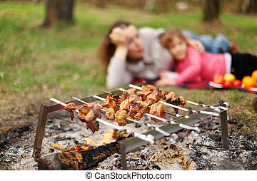 Mother and daughter lie near campfire with grill and barbecue; focus on meat