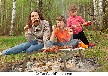 Mother and her children eat grilled shish kebab outdoor; focus on mother