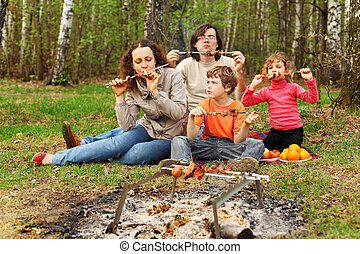 Mother, father and children eat grilled shish kebab outdoor;...