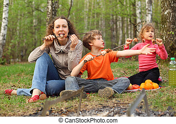 Mother and her children finish to eat grilled shish kebab outdoor; focus on mother