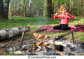 Girl sits near campfire with grill and barbecue and eats...