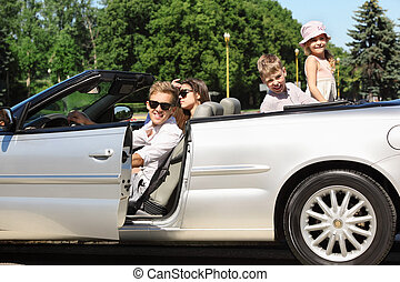 Happy father, mother and two children sit in beautiful convertible car