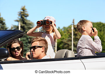 Young father, mother and two children ride in convertible...