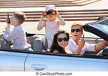 Happy father, mother and two children ride in convertible...