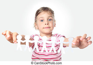 beautiful little girl holding garland of paper little people in outstretched hands isolated on gray