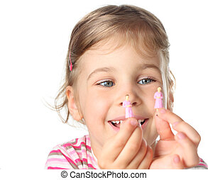 beautiful little girl holding small toy figures of woman and...