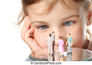 beautiful little girl looks at small toy figures of people...