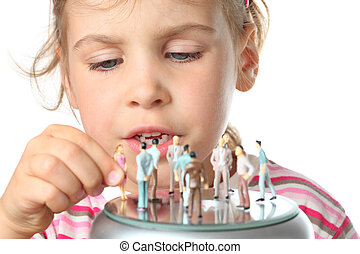 beautiful little girl plays with small toy figures of people...