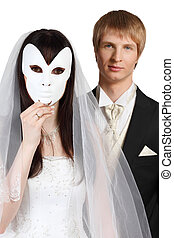 Beautiful bride hid her face behind white mask; groom stands...