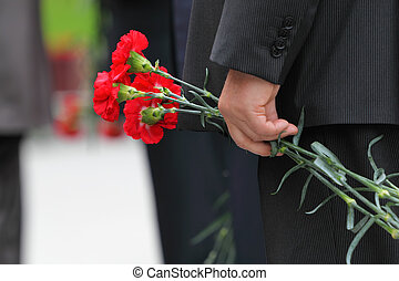Bouquet of red carnations in man hand at Victory Day...