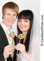 Happy young groom and bride hold colorful lollipops on white...