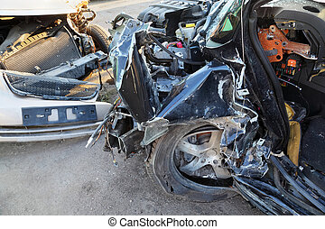 Crumpled and broken hoods of two collided cars after...