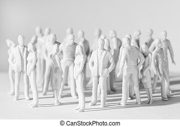 white miniature toy people stand in different poses, men and...