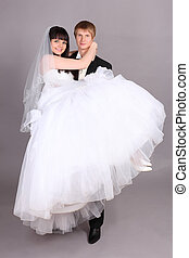 Young groom holds beautiful bride in studio on gray background