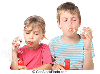 little boy and girl sitting and blowing bubbles isolated on white