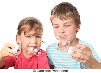 little brother and sister sitting, smiling and blowing bubbles isolated on white