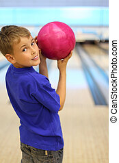 Smiling boy dressed in blue T-shirt holds pink ball in...