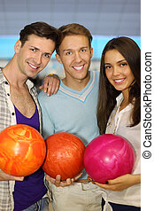 Two young men and beautiful girl hold balls in bowling club;...