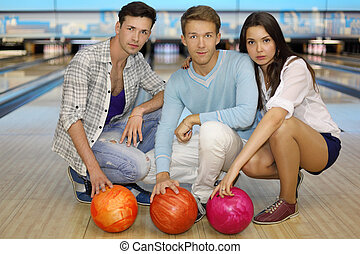 Two young men and girl sit on floor with balls in bowling club; focus on center man; shallow depth of field