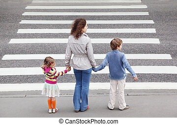 young mother holds hand of his little daughter and son and...