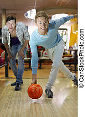 Young smiling man throws ball in bowling; friend looks at aim; shallow depth of field