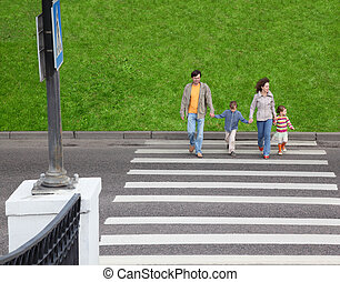 mother and father holds hand of little daughter and son and crossing road