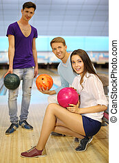 Two young men and girl with balls in bowling club; left man stands and others sit; shallow depth of field; focus on woman