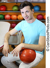 Young smiling man sits at table near shelves with balls and holds red ball in bowling club; shallow depth of field