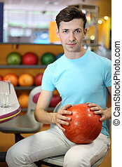 Young man sits at table with glass with water near shelves with balls and holds red ball in bowling club; shallow depth of field