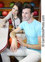 Beautiful brunette woman and man sit at table and look up in bowling; girl holds glass with pure water and man holds red ball; focus on man; shallow depth of field