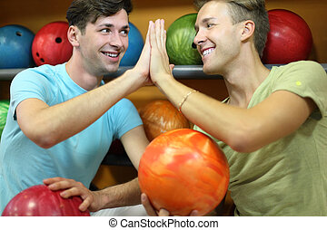 Two happy men sit near shelves with balls and touch hands in bowling club; focus on right man; shallow depth of field
