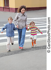 young mother holds hand of little daughter and son and...