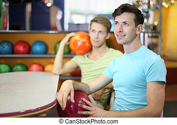 Two men sit at table in bowling, hold balls and look up;...