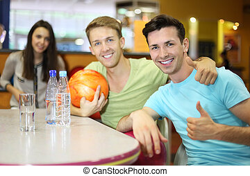 Two men and woman with balls sit at table in bowling and men thumb up; two bottles and glass with water on table; focus on right man; shallow depth of field