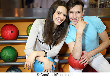Man and woman sit near shelves with balls and hold balls in...