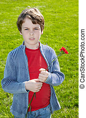 Boy in the red t-shirt with red carnation in the hands stands on the green grass background.