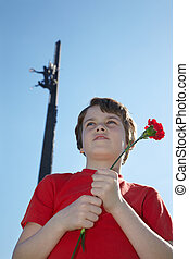 Boy stands on Poklonnaya Hill with red carnation in the hands on the background of Victory Monument on the Victory Day.