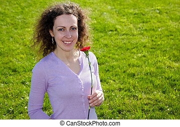 Attractive smiling young girl with red carnation in the hands stands on the green lawn