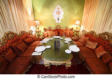 beautiful table with serving and red sofas in eastern luxury...